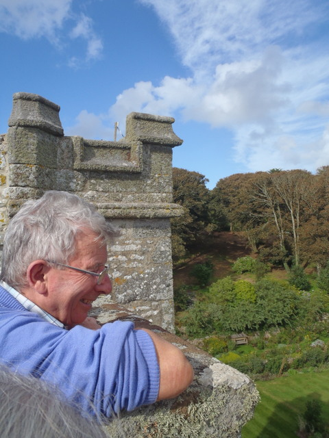 man looking over a castellated wall and smiling